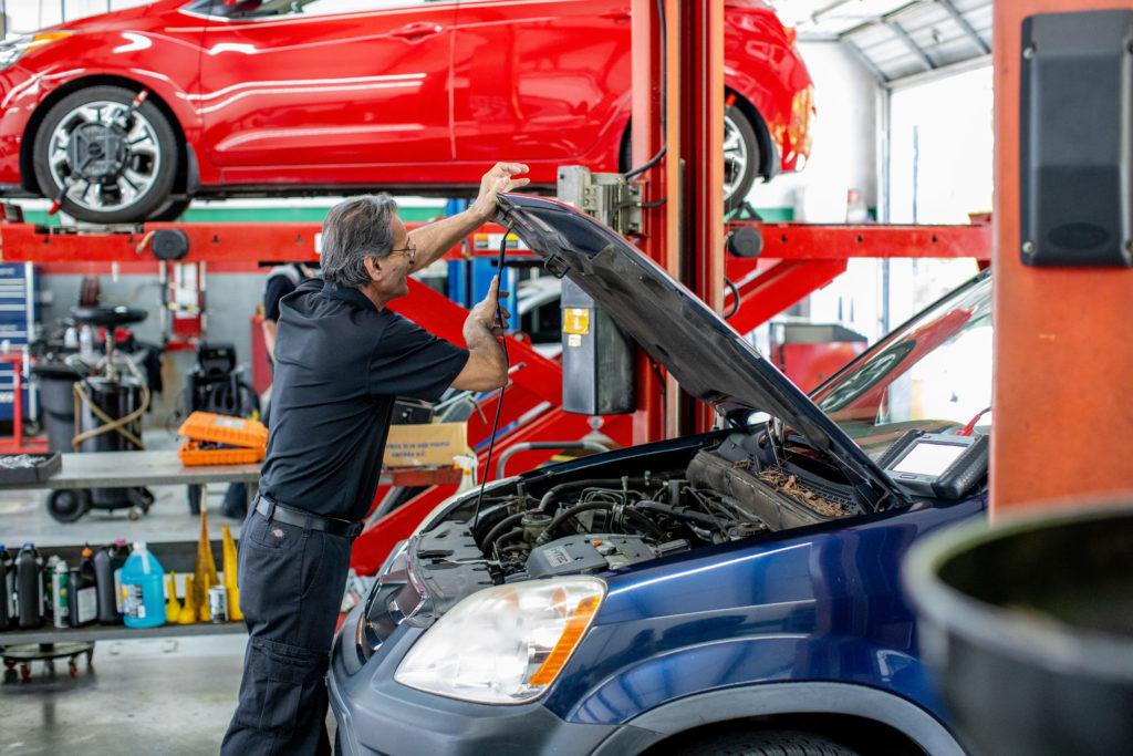 Technician propping up car hood